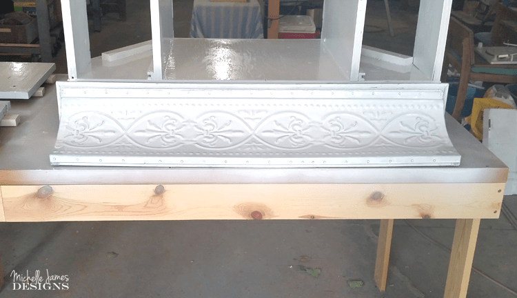 Painting the metal shelf with the white chalk paint.
