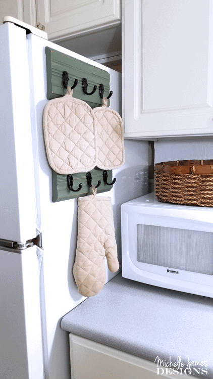 I used a piece of trim from a garage sale to create an upcycled kitchen oven mitt organizer. I love it! - www.michellejdesigns.com