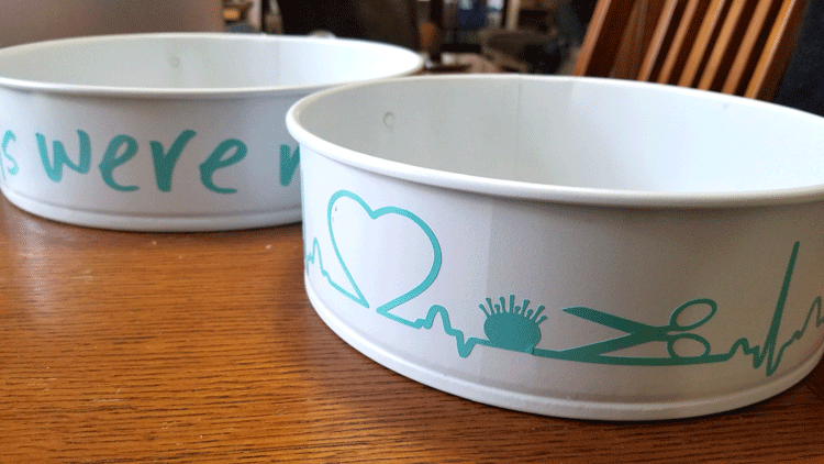 White painted pans with teal vinyl designs on the sides.