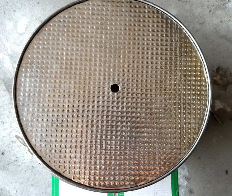 Bottom of springform pan with a hole drilled in the center