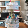 Photo of full upcyled tiered craft organizer full of tools with craft space in the background.