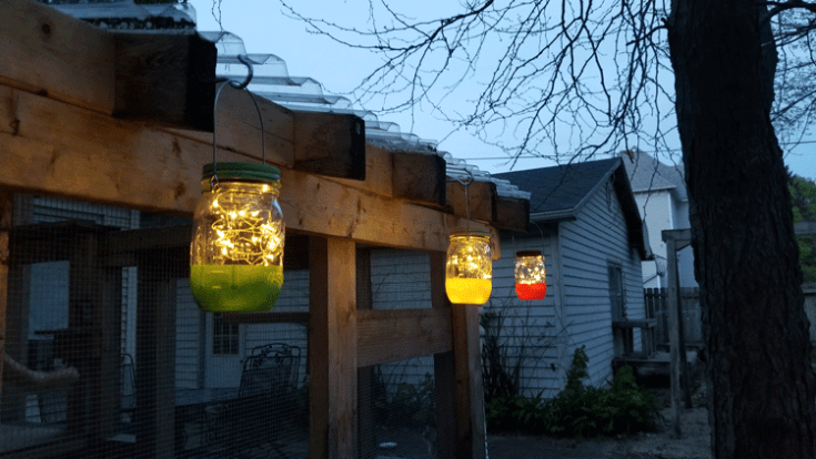 Colorful hanging mason jar solar lights lit up just as it begins to get dark