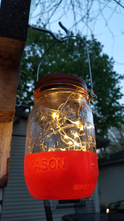Looking up at the red hanging jar light with the solar fariry lights