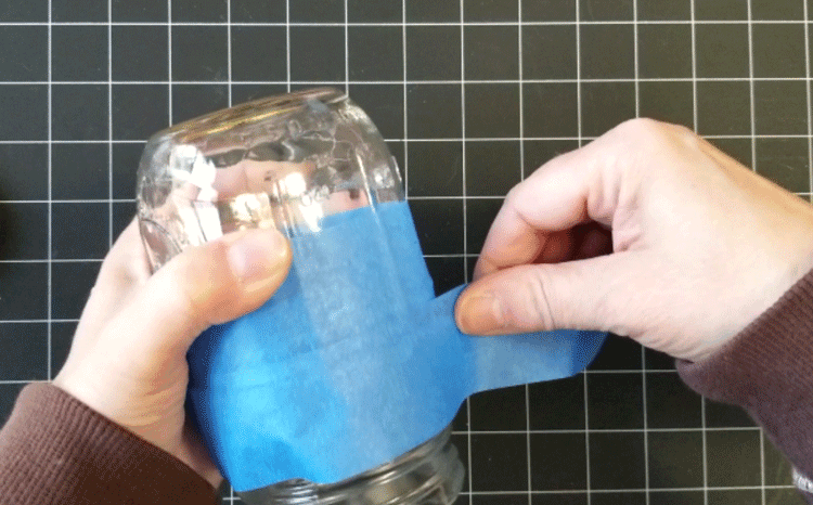 Using painters tape to mask off the area of the jar that doesn't get painted.