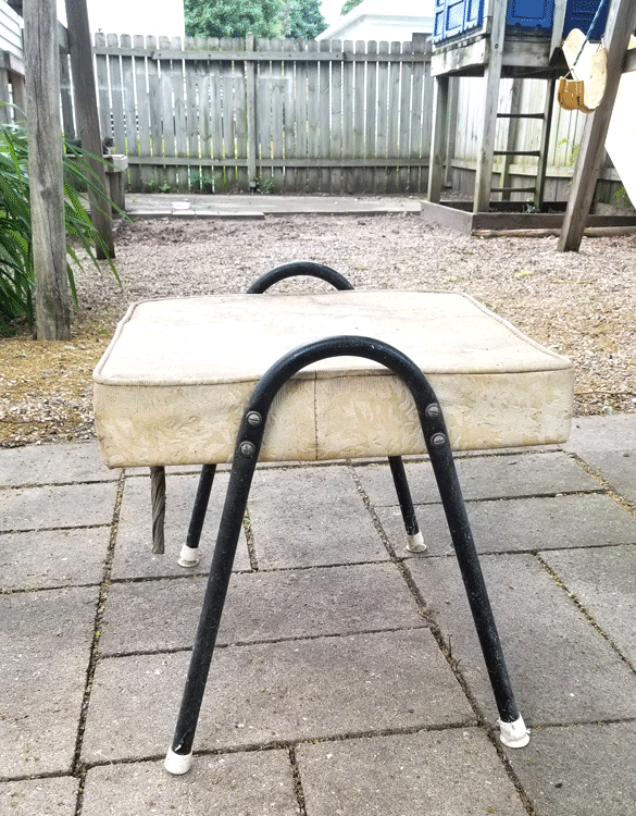 The outdoor ottoman before the project begins. An old dirty cream colored cushion with black metal legs.