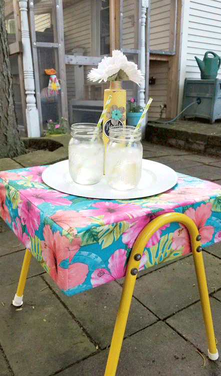 Colorful ottoman in the patio with a tray, water and an upcycled vase with daisies.