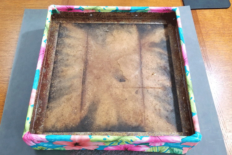 Shows the underside of the top cushion. It is rusty and old with the new vinyl table cloth covered and glued on the edges.