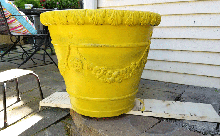 A large foam flower pot after one coat of the harvest yellow color. Some of the black is still showing under the paint.