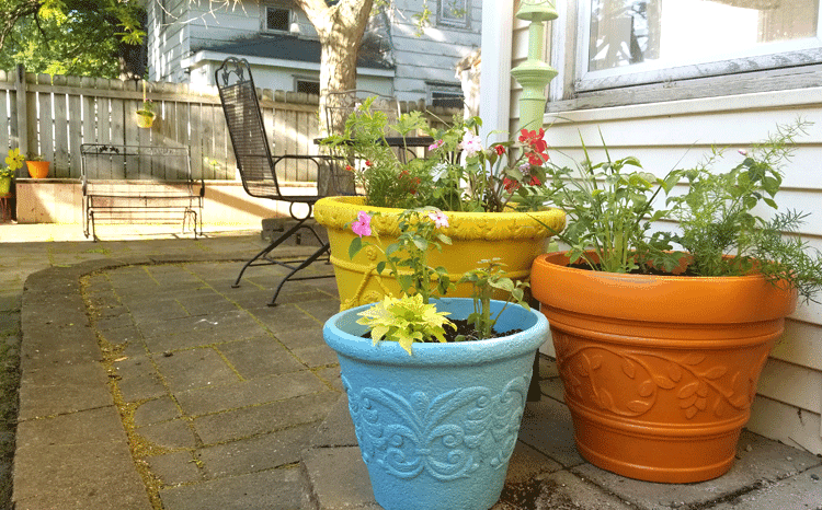 Three large foam planters at the backdoor filled with plants with the patio space and fence in the background.