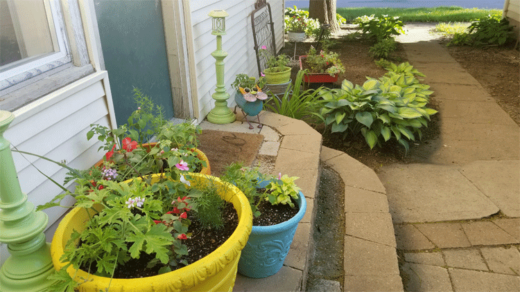 Three large foam flower pots at the backdoor with the radio flyer wagon filled with plants in the background.