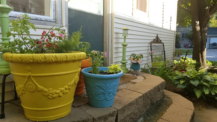 The three large foam planters by the backdoor with solar lamp posts in the background.