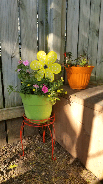 Green and orange painted plastic flower pots with a variety of flowers and a large yellow fabric flower that spins in the wind.