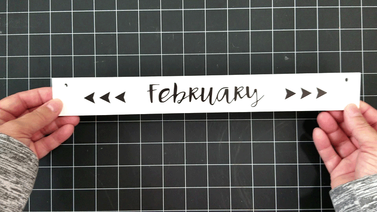 The month of February text cut from vinyl and added to the calendar piece that hangs at the top.