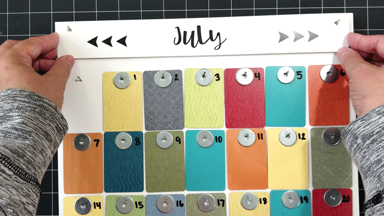 Adding the finished month piece to the calendar by hanging it onto two nails.