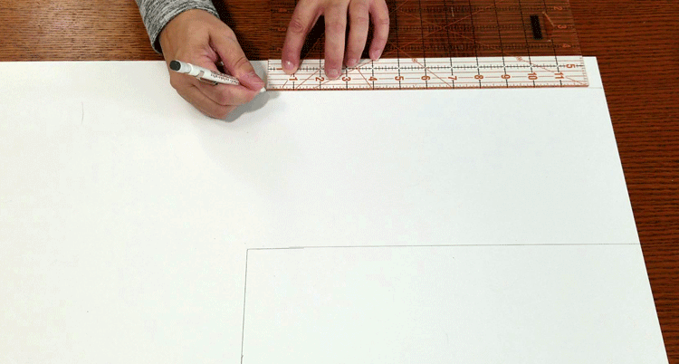 Drawing out the cut lines on the piece that will be come the wall calendar.