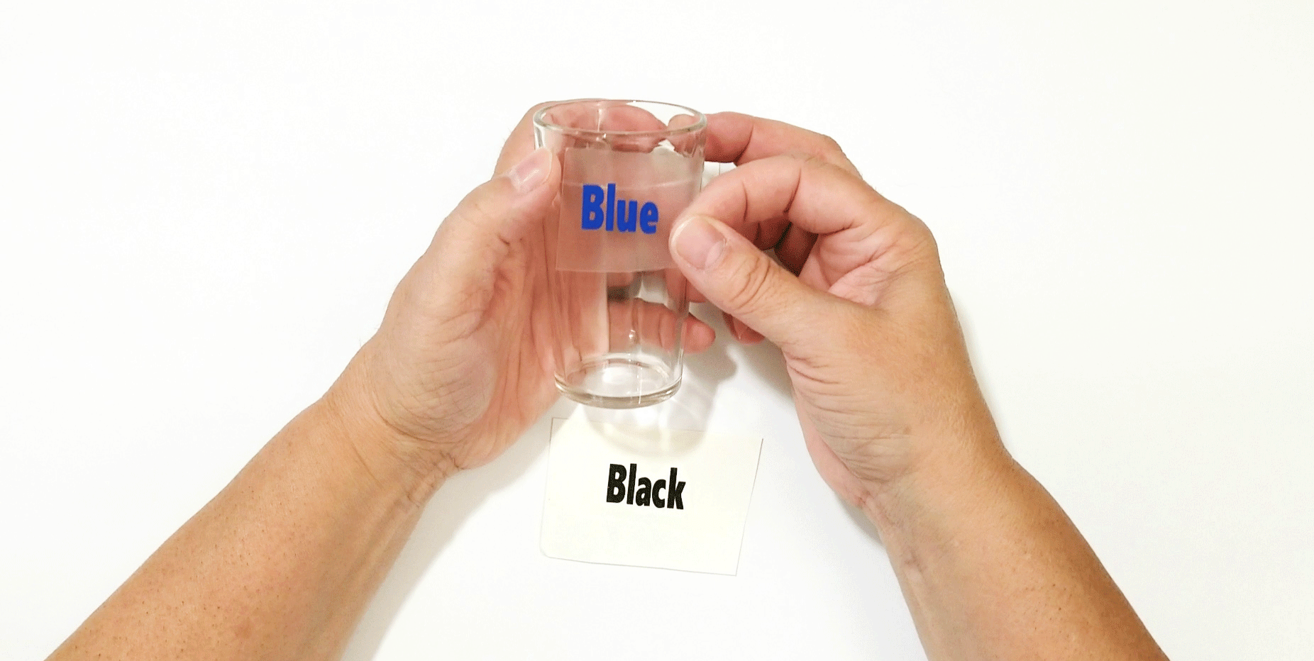 "Placing the vinyl word ""blue"" onto the small glass juice cup."