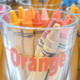 Orange crayons in a glass cup labeled with orange vinyl that says orange.