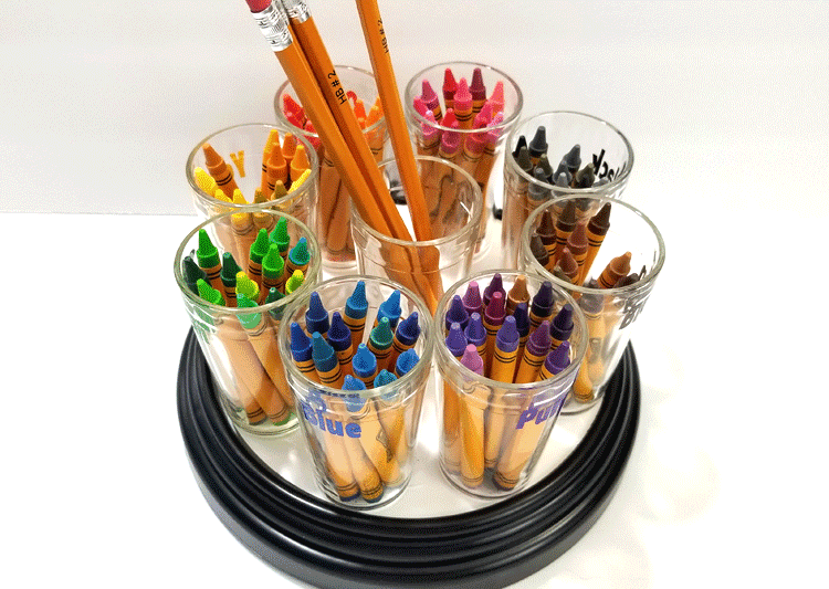 All of the colors of crayons separated into families and placed on the crayon holder carousel.