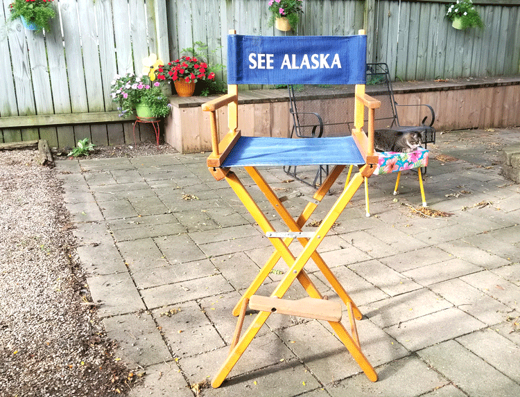 Light wood directors chair with blue canvas seat and back. The back says See Alaska