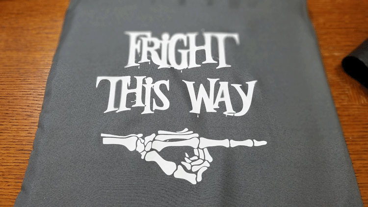 Fright this way cut from white iron on vinyl and pressed onto gray fabric.
