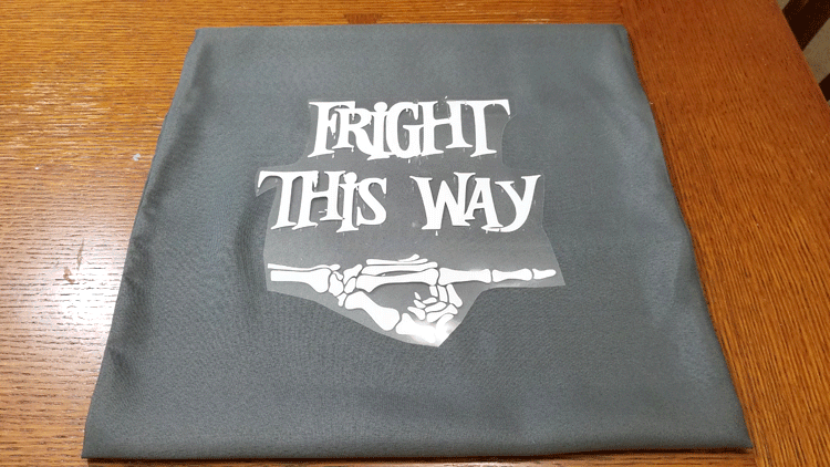 Fright this way cut from white iron on vinyl ready to press onto gray fabric.