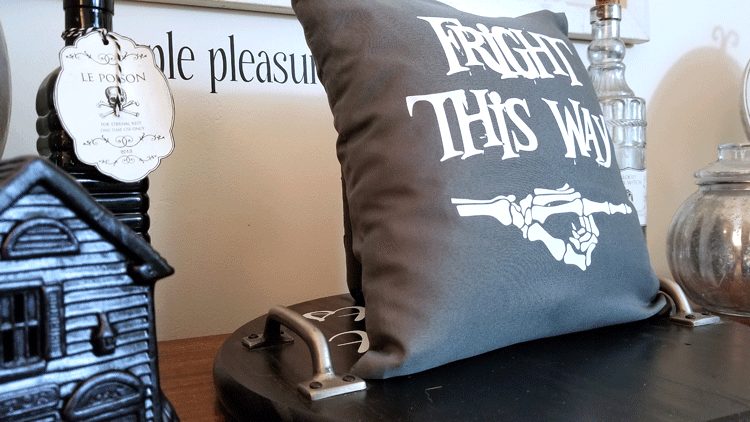 "Gray and white ""Fright This Way"" pillow staged on wood desk with haunted house village and potion bottles"