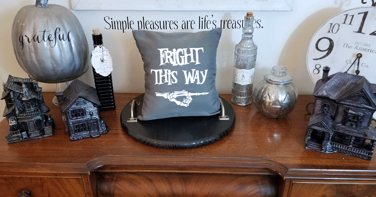 "Gray and white ""Fright This Way"" pillow staged on wood desk with haunted house village and potion bottles."