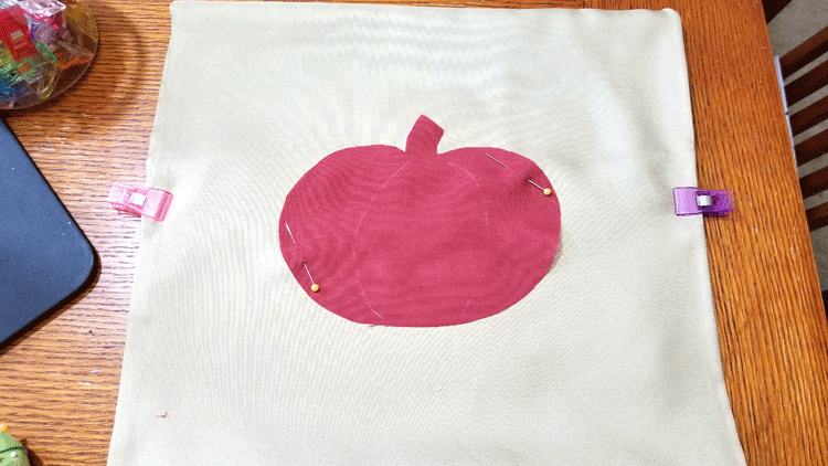 Pinning the pumpkin onto the fabric for stitching.