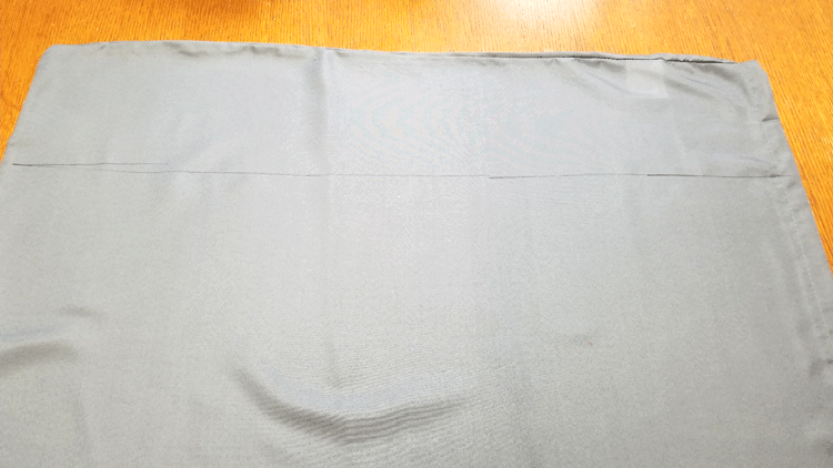 Gray fabric with the cut line ready to cut to size for pillow cover