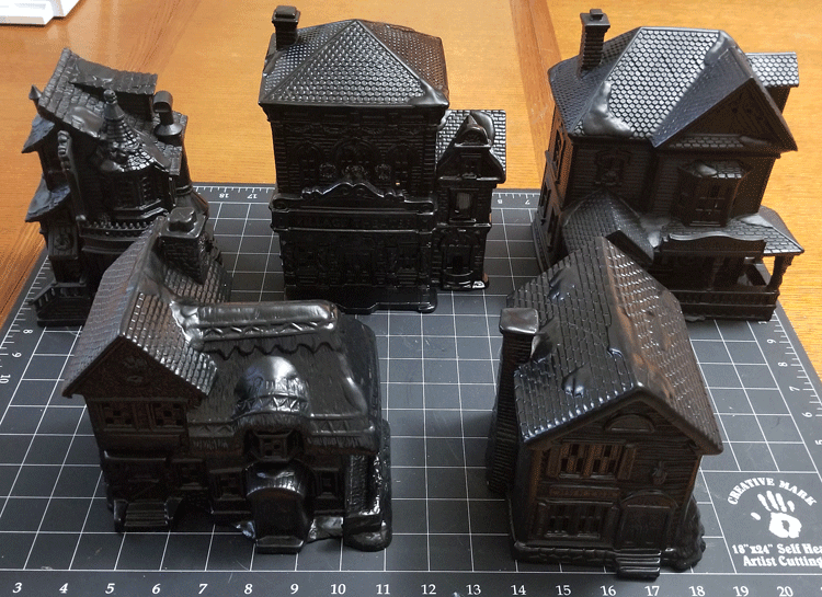 Christmas village pieces painted black to become a Halloween Village set.