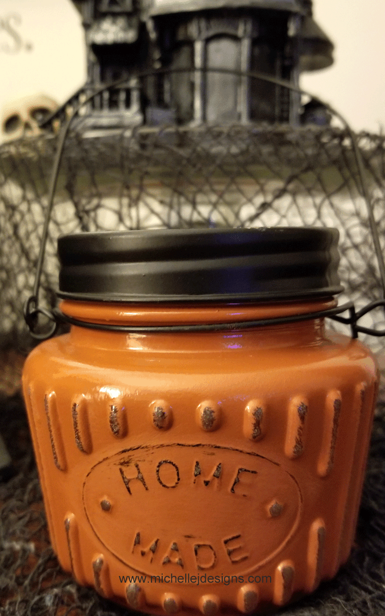 Close up of the finished pumpkin tea light with a spooky halloween village piece behind it.