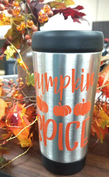 Travel mug with pumpkin spice latte and whipped cream
