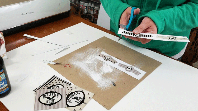 Cutting out the printed beer bottle labels.