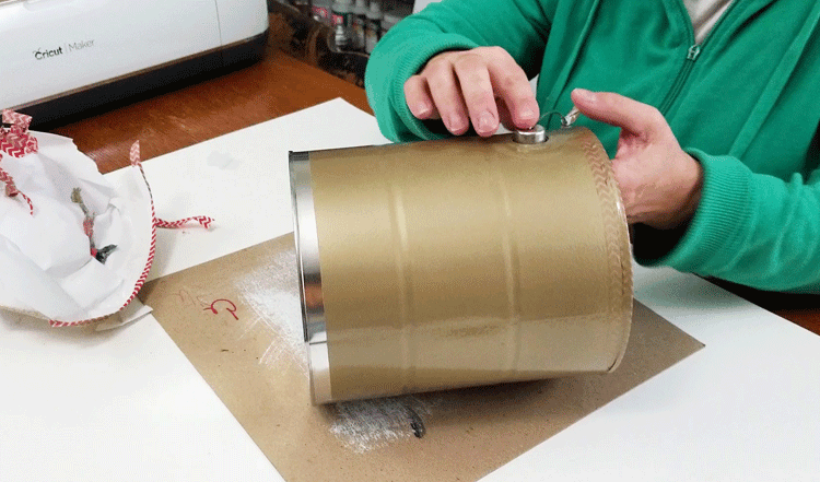 Removing mask/tape from the paint can.