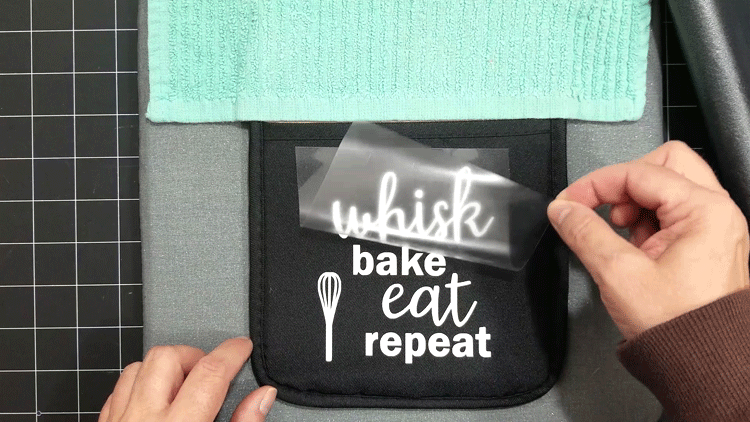 Removing the backing from the design after using the Easy Press to adhere it to the oven mitt