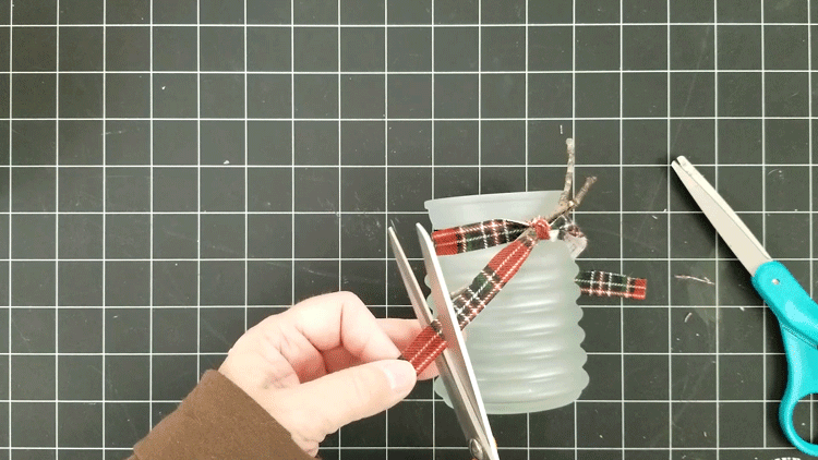 Trimming the ends of the plaid fabric ribbon to length.