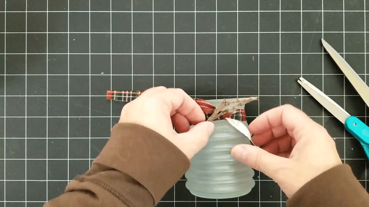 Adding fabric strip and sticks to the neck of the candle holder