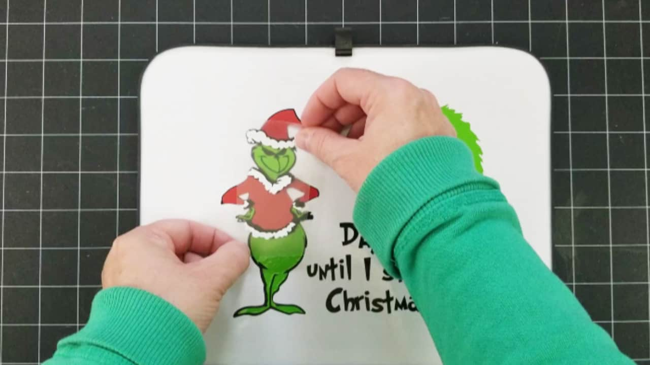 Adding the white layer of vinyl to the Grinch design.