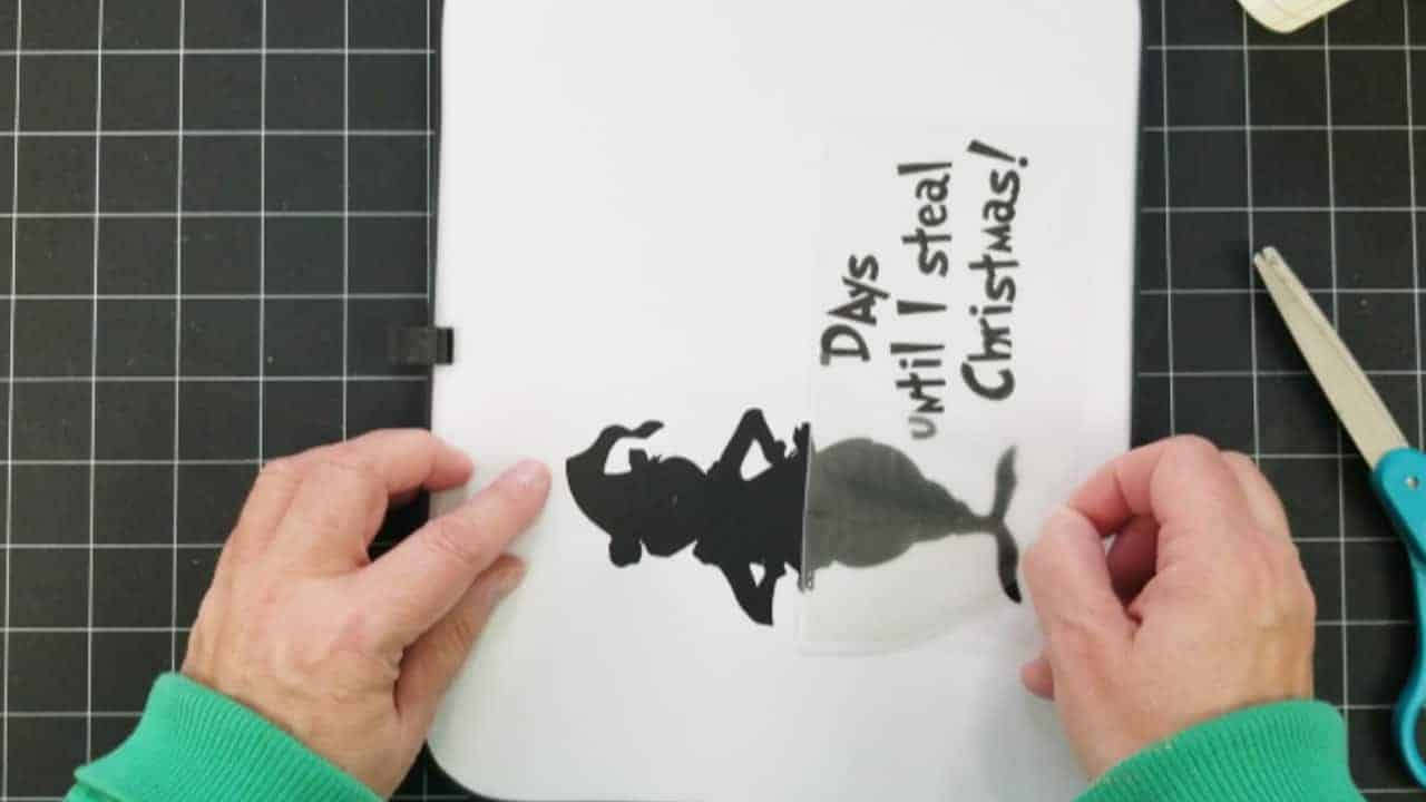 Removing the transfer tape from the black vinyl after placing onto the dry erase board.