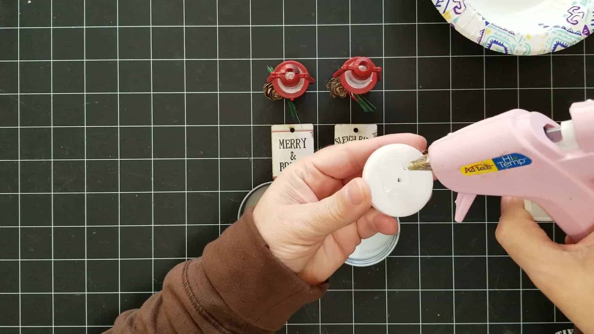 Gluing foam pieces with the hot glue gun to add into the lid of the mason jar ornament.