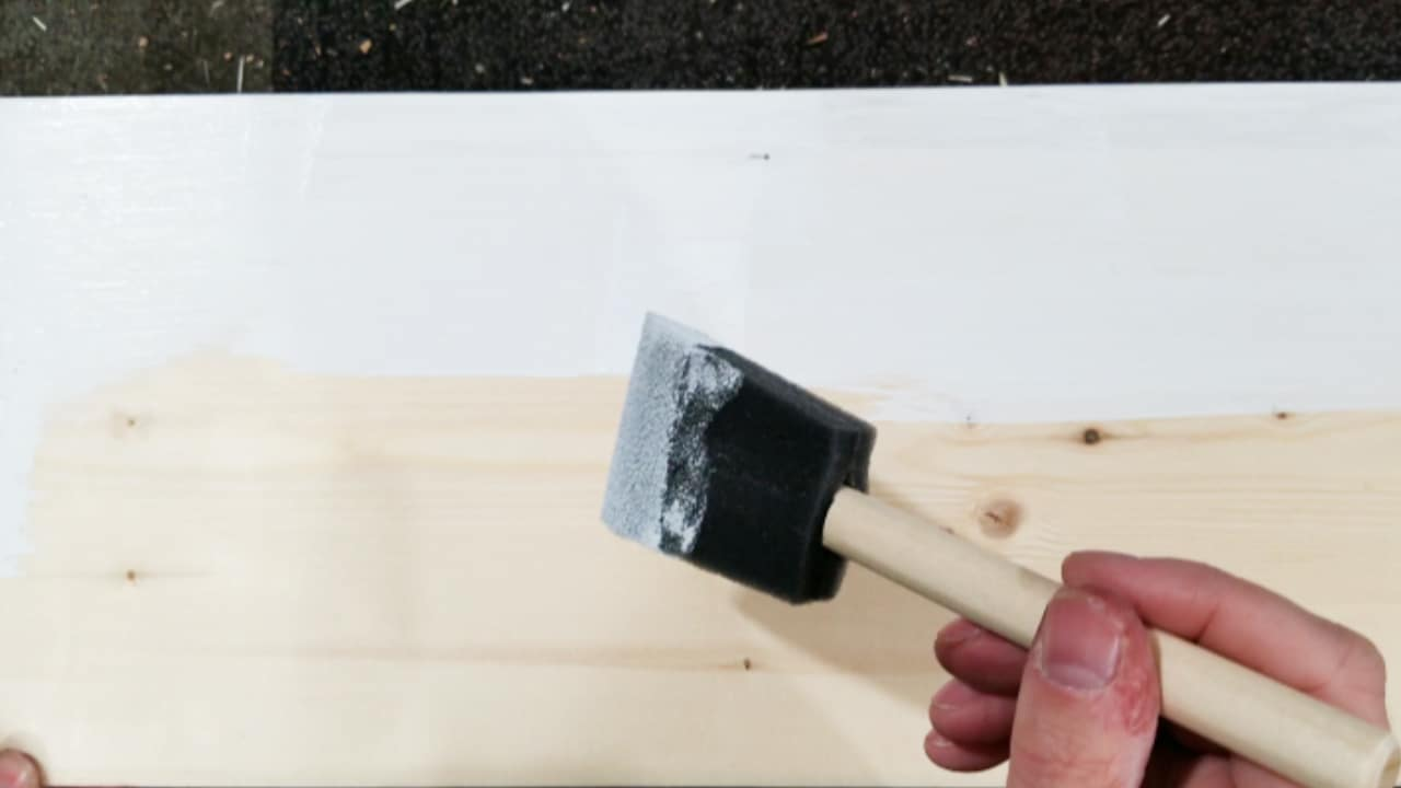 White paint being brushed onto the cut and sanded wood piece.