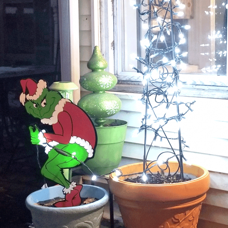Finished Grinch Yard Art stealing the lights from my tree.