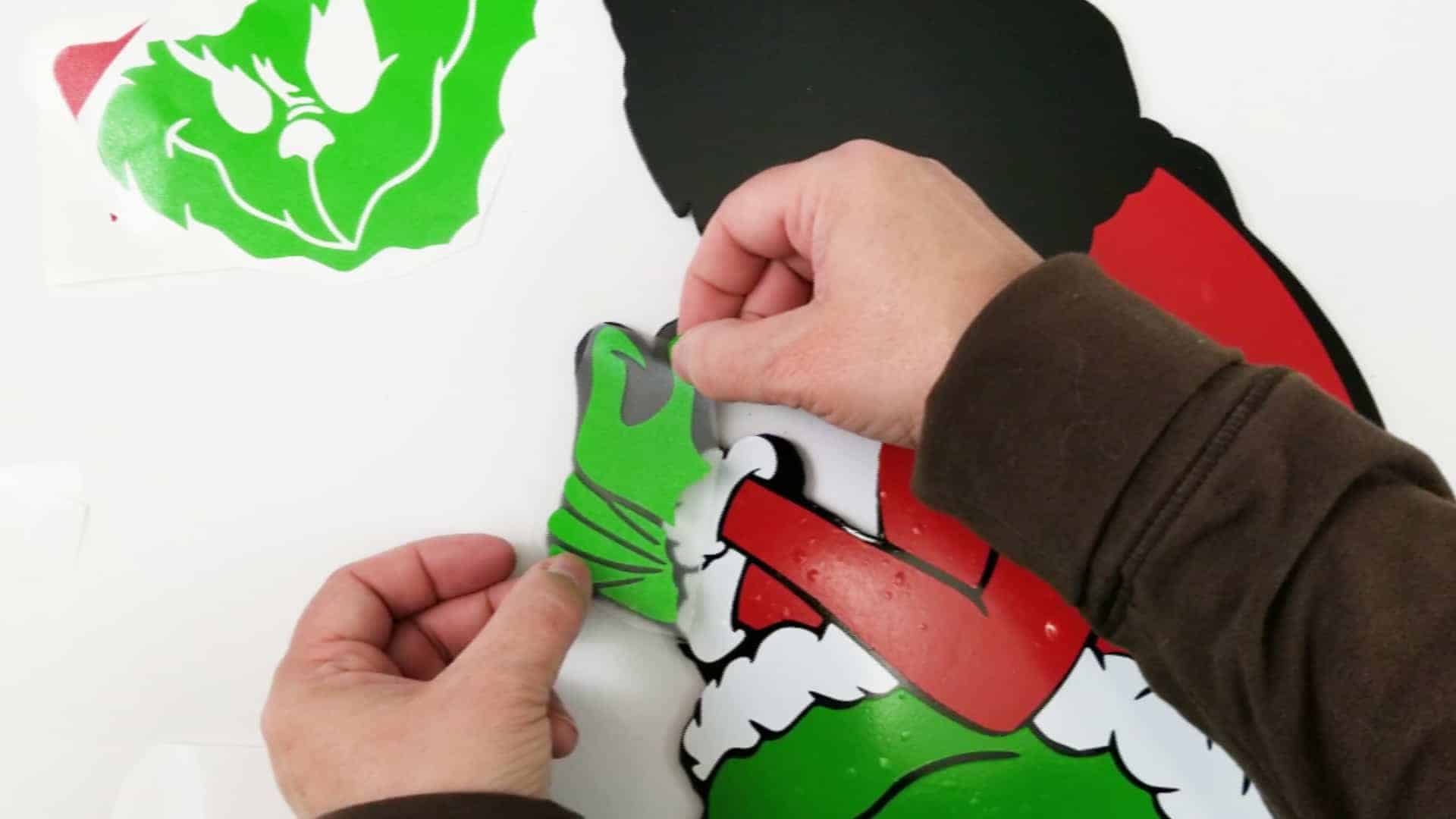 Adding red, white and green vinyl pieces to a black Grinch outline to complete the Grinch yard art
