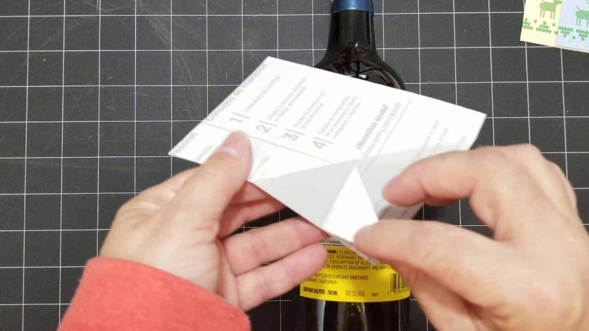Peeling off the backing of the sticker paper to adhere the holiday wine label.