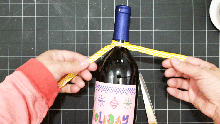 Tying a bright, yellow ribbon around the neck of the ugly sweater wine label bottle