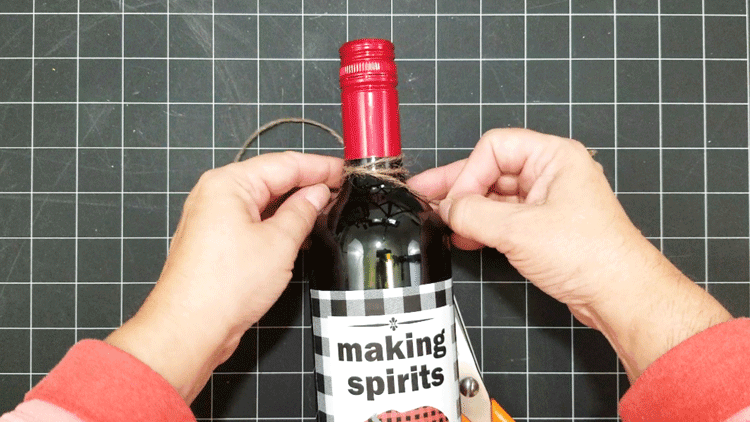 Tying a piece of jute twine around the neck of the bottle to add a finishing touch to the buffalo check holiday wine label.