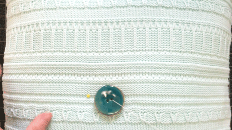Adding a large teal button to the center of a square sweater pillow
