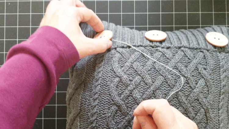 Hand stitching a wood button onto a gray sweater pillow