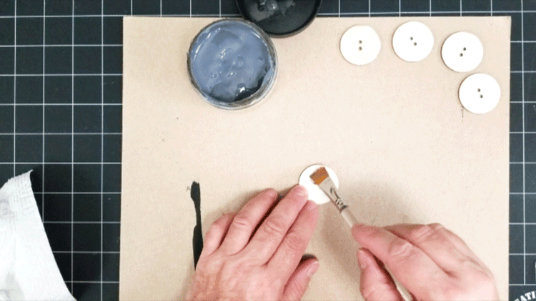 Painting grunge stain onto wood buttons that will be added to sweater pillows