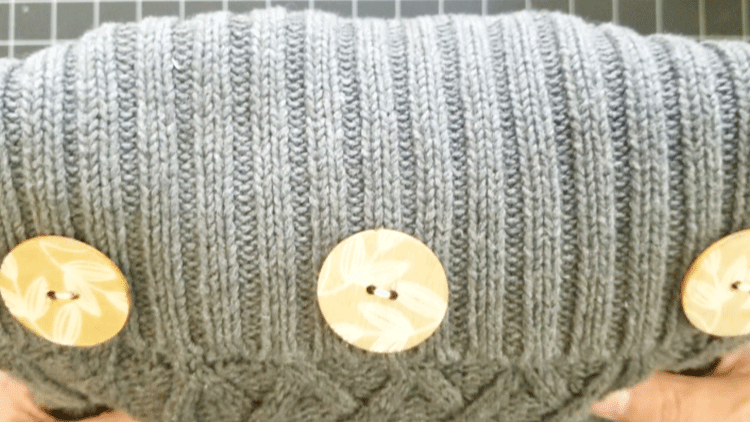 Showing the three wood buttons at the top of a gray sweater pillow